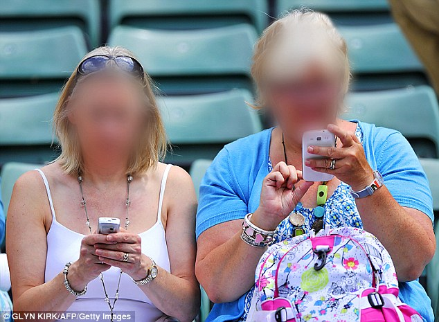 It's much better on the small screen: Tennis spectators check their phones in their seats at Wimbledon